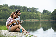 Relaxed young couple with coffee mugs sitting on a jetty at lake looking at distance - ZOCF000052