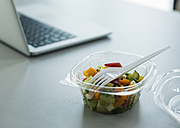 Plastic bowl with salad on desk in office - UUF007090