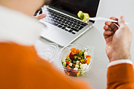 Young man having a salad at desk in office - UUF007102