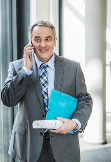 Smiling senior businessman on cell phone - UUF007126