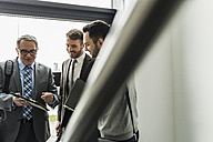 Three businessmen with digital tablet talking in staircase - UUF007141