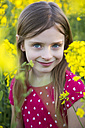 Portrait of smiling girl in a rape field - SARF002698
