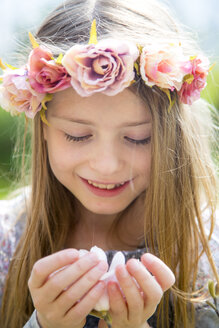 Portrait of smiling girl with wreath of flowers holding magnolia blossom in her hands - SARF002700