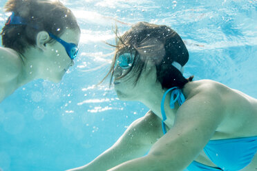 Boy diving underwater with his mum, swimming pool - ZOCF000070