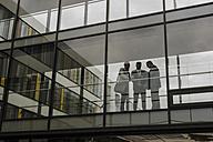 Three businessmen behind glass facade - UUF007166