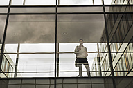 Businessman with mobile phone, standing in passage - UUF007172