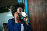 Portrait of young woman talking on mobile phone while drinking coffee in a street cafe - KIJF000339