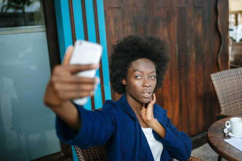 Portrait of young woman taking a selfie with smartphone in a street cafe - KIJF000342