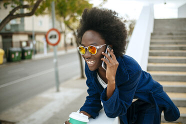 Portrait of young woman wearing mirrored sunglasses talking on mobile phone - KIJF000345