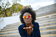 Portrait of young woman wearing mirrored sunglasses throwing a kiss to camera - KIJF000348