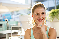 Portrait of smiling young woman at outdoor cafe in summer - ZOCF000077