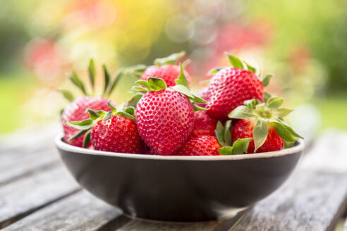 Bowl of strawberries on wooden garden table - SARF002705