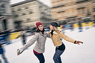 Two happy friends skating on outdoor ice rink - ZOCF000083