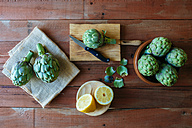 Raw artichokes and sliced lemon on wood - KIJF000351