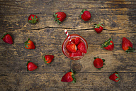 Glass of strawberry smoothie and strawberries on dark wood - LVF004811