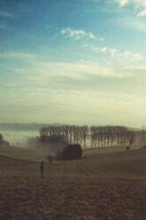 Gernany, North Rhine-Westphalia, man standin in field - DWIF000729