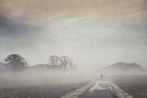 Gernany, North Rhine-Westphalia, Silhouette of a man standing on foggy country road - DWIF000735