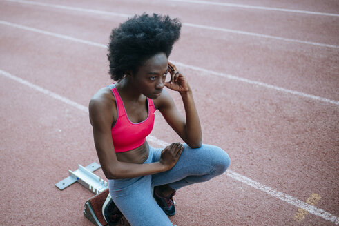 Young black athlete preparing for race in stadium - KIJF000374