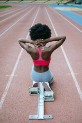 Young black athlete preparing for race in stadium - KIJF000377