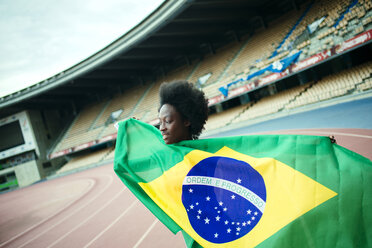 Young black athlete in stadium carrying Brazilian flag - KIJF000380