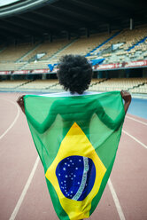 Young black athlete in stadium carrying Brazilian flag - KIJF000383