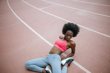 Young black athlete stretching before race in stadium - KIJF000386