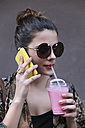 Portrait of young woman drinking smoothie while telephoning with smartphone - RTBF000158