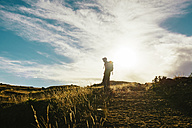 Peru, Amantani Island, silhouette of man with backpack hiking at sunset - GEMF000880
