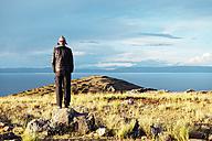 Peru, Amantani Island, man looking  from Pachamama peak to Pachatata - GEMF000883