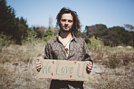 Hippie holding 'We love you' sign in the nature - GIOF000897