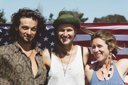 Portrait of three smiling hippies with US flag - GIOF000900