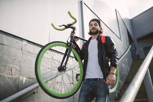 Young man carrying fixie bike - RAEF001084