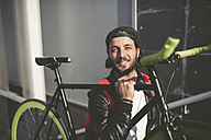 Smiling young man carrying fixie bike - RAEF001096