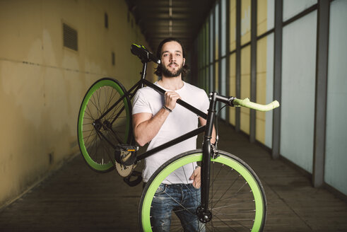 Young man carrying fixie bike - RAEF001117