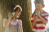 Little boy and girl playing with tin can phone in nature - ZOCF000116