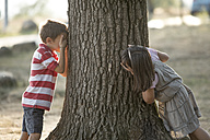 Little boy and girl playing hide and seek in nature - ZOCF000119