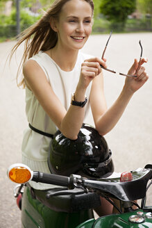 Portrait  of smiling young woman with moped and motorcycle helmet - CHAF001656