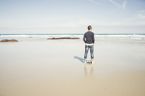 Spain, Ribadeo, Young man on Las Catedrales Beach on a spring day - EPF000081