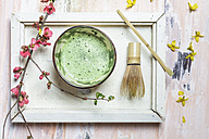 Matcha tea in bowl, with match powder, spoon and chasen and pink flowers - SBDF002861