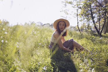 Young woman wearing straw hat sitting on a meadow - GIOF000912