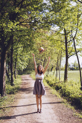 Happy young woman throwing her summer hat into the air - GIOF000927