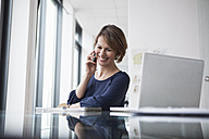 Smiling businesswoman on cell phone at office desk - RBF004418