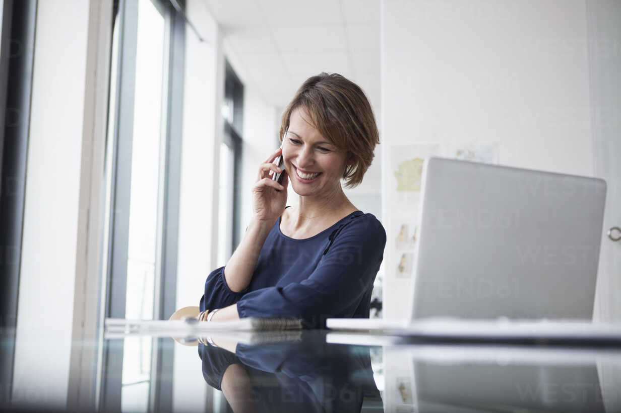 Smiling businesswoman on cell phone at office desk - RBF004418 - Rainer Berg/Westend61