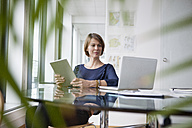 Businesswoman with digital tablet and laptop at office desk - RBF004421