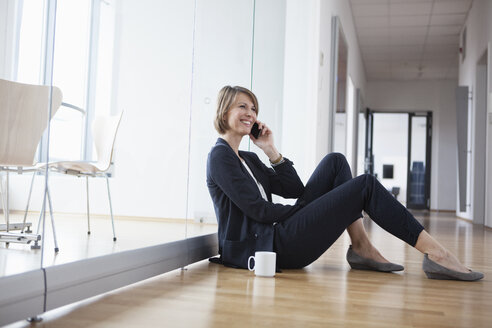 Businesswoman resting on office floor talking on cell phone - RBF004448