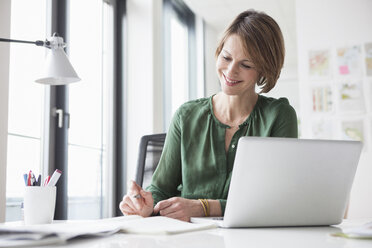 Smiling businesswoman working at office desk - RBF004457