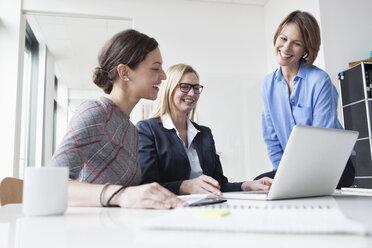 Three happy businesswomen sharing laptop in office - RBF004511