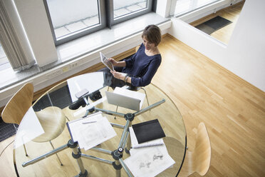 Businesswoman with digital tablet and laptop at office table - RBF004526
