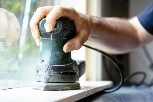 Man sanding a windowsill - HAWF000887