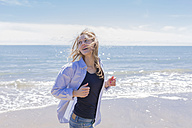 Portrait of smiling young woman running at seaside - BOYF000291